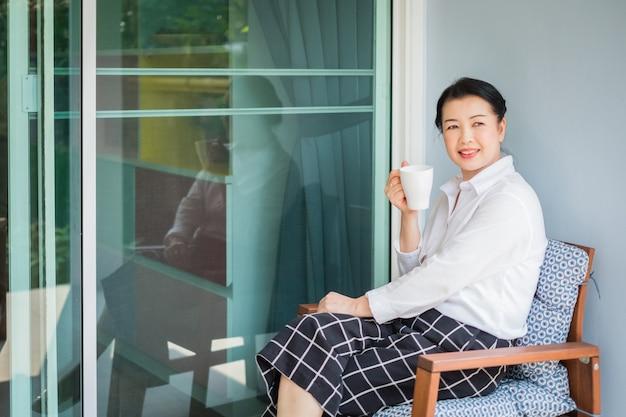 Kobieta siedzi w fotelu i picia kawy w domu rano