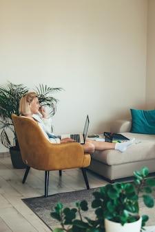 Kobieta siedzi w fotelu i rozmawia przez telefon