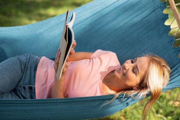 Kobieta siedzi w hamaku i czyta wysoki widok