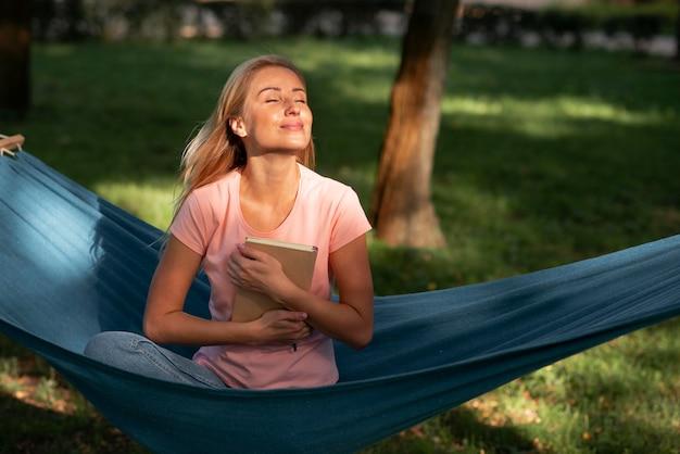Kobieta siedzi w hamaku i trzyma książkę