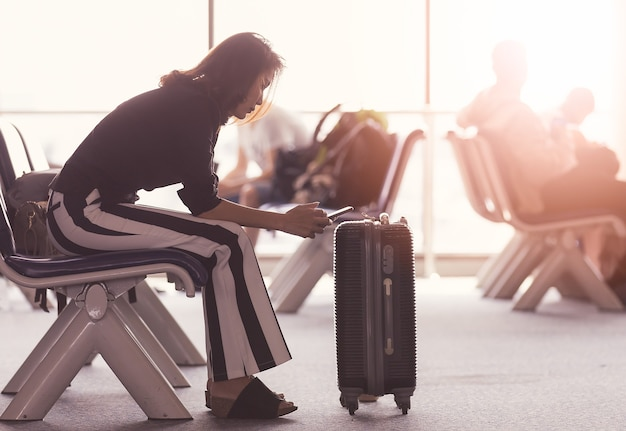 Kobieta siedzi w holu lotniska za pomocą smartfona i patrząc na ekran podczas oczekiwania na tranzyt. światło słoneczne wpadające z zewnątrz.