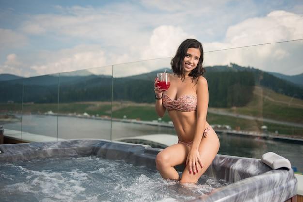 Kobieta siedzi w jacuzzi przy koktajlu