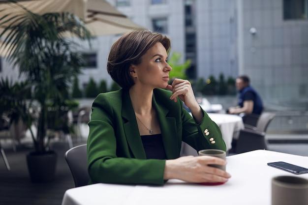 Kobieta siedzi w kawiarni i odpoczywa po wszystkich spotkaniach i wywiadach. zielona stylowa marynarka i czarna bluzka, krótka fryzura, makijaż cielisty. kubek gorącej kawy