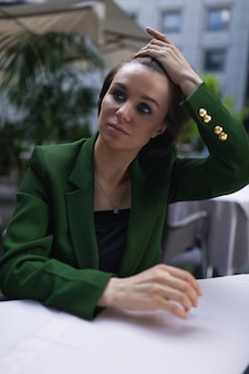 Kobieta siedzi w kawiarni i odpoczywa po wszystkich spotkaniach i wywiadach. zielona stylowa marynarka i czarna bluzka, krótka fryzura, makijaż cielisty.