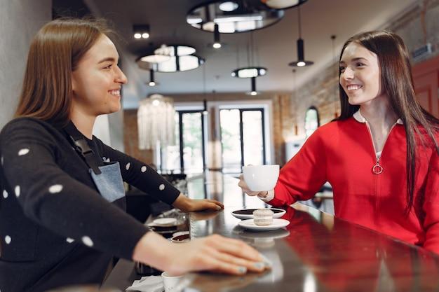Kobieta siedzi w kawiarni i rozmawia z baristą