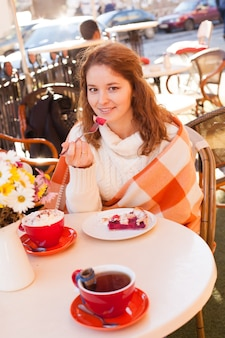 Kobieta siedzi w kawiarni na świeżym powietrzu i je ciasto i kakao, przytulna jesień