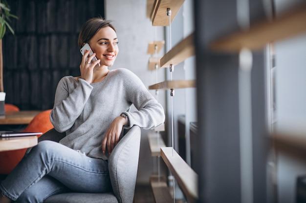 Kobieta siedzi w kawiarni picia kawy i pracy na komputerze