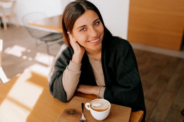 Kobieta siedzi w kawiarni pije filiżankę kawy