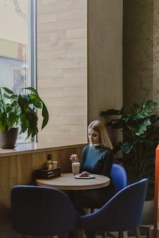 Kobieta siedzi w kawiarni rano z kawą i rogalikiem