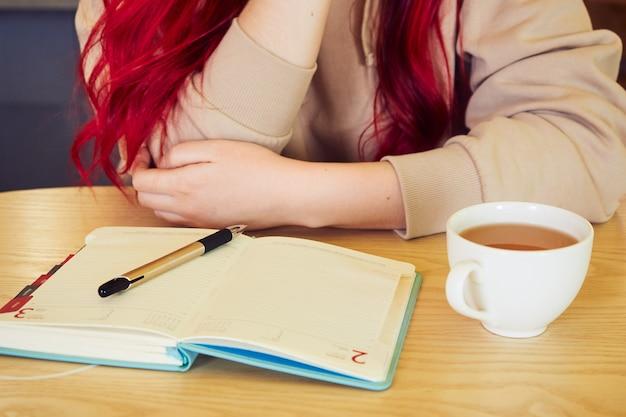 Kobieta siedzi w kawiarni z otwartym pamiętnikiem przy filiżance herbaty