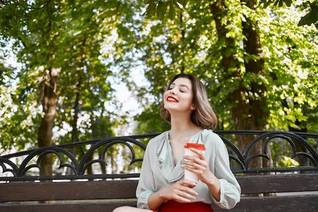 Kobieta siedzi w letnim parku z filiżanką kawy na świeżym powietrzu