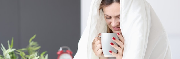 Kobieta siedzi w łóżku pod kołdrą i pije herbatę śniadanie w koncepcji łóżka