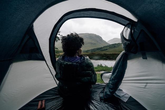 Kobieta siedzi w namiocie, podczas gdy pada deszcz