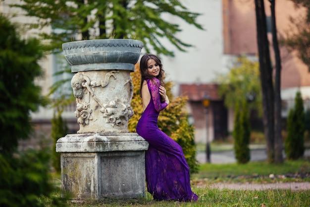 Kobieta siedzi w pobliżu kolumny z fioletową sukienkę