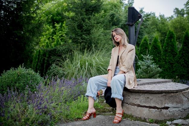 Kobieta siedzi w pobliżu kwiatów lawendy w ogrodzie