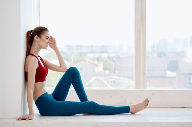 Kobieta siedzi w pobliżu okna medytacja relaks zdrowie joga