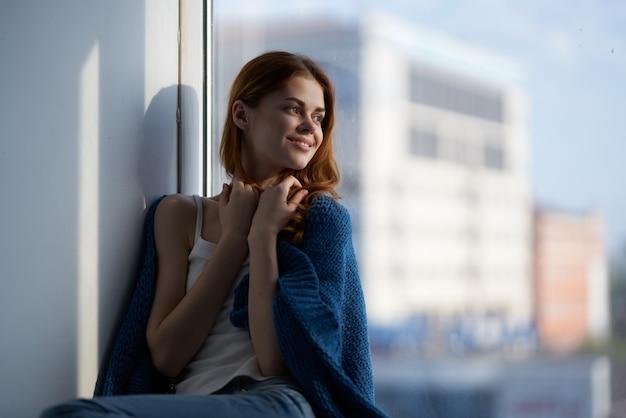 Kobieta siedzi w pobliżu okna z marzycielski wygląd niebieskiej kraty. zdjęcie wysokiej jakości