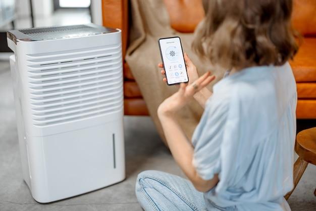 Kobieta siedzi w pobliżu urządzenia oczyszczającego powietrze i nawilżającego w pobliżu kanapy monitorującej jakość powietrza w smartfonie. pojęcie mikroklimatu zdrowia w domu. widok z tyłu