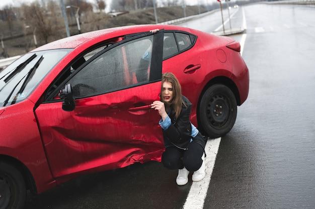 Kobieta siedzi w pobliżu uszkodzonego samochodu po wypadku. zadzwoń po pomoc. ubezpieczenie samochodu