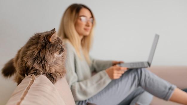 Kobieta siedzi w pomieszczeniu z kotem
