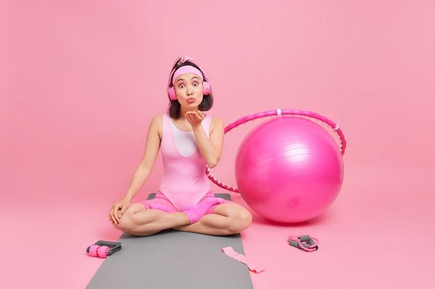 Kobieta siedzi w pozycji lotosu wysyła pocałunek do kamery wyraża miłość nosi opaskę na głowie wygodne body słucha muzyki przez słuchawki pozuje na karemacie ze sprzętem sportowym dookoła