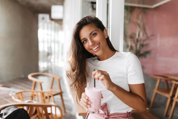 Kobieta siedzi w przytulnej kawiarni i miesza truskawkowy koktajl