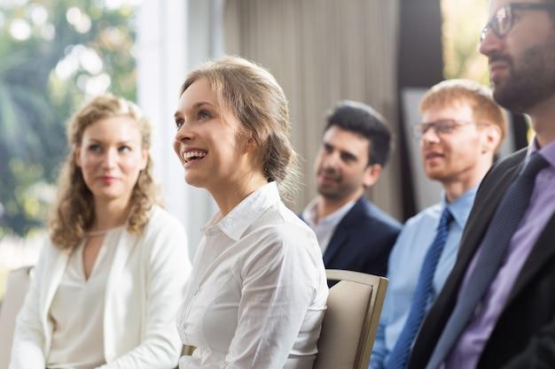 Kobieta siedzi w publiczności uśmiechając
