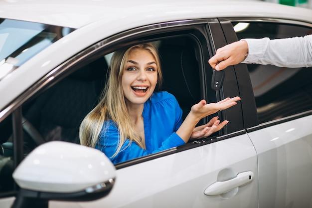 Kobieta siedzi w samochodzie i odbiera klucze w salonie samochodowym
