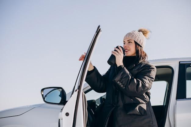Kobieta siedzi w samochodzie i pije kawę