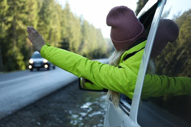 Kobieta siedzi w samochodzie w świerkowym lesie i macha