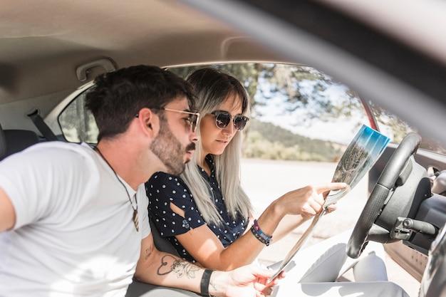 Kobieta siedzi w samochodzie, wskazując miejsce docelowe na mapie swojego chłopaka