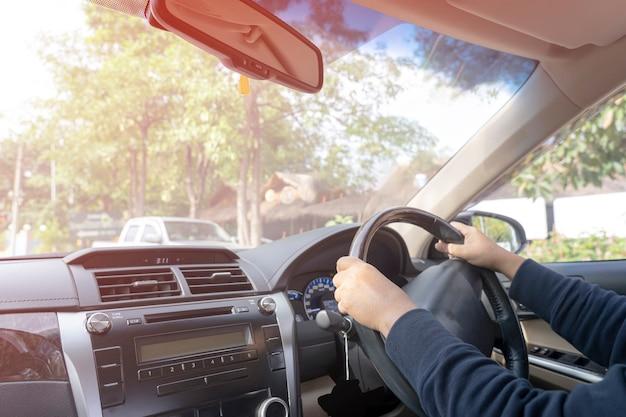 Kobieta siedzi w samochodzie z dwiema rękami na kierownicy