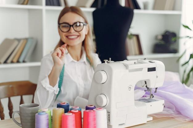 Kobieta siedzi w studio i szyć tkaniny