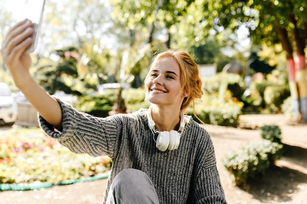 Kobieta siedzi w szklarni bierze selfie na swoim telefonie