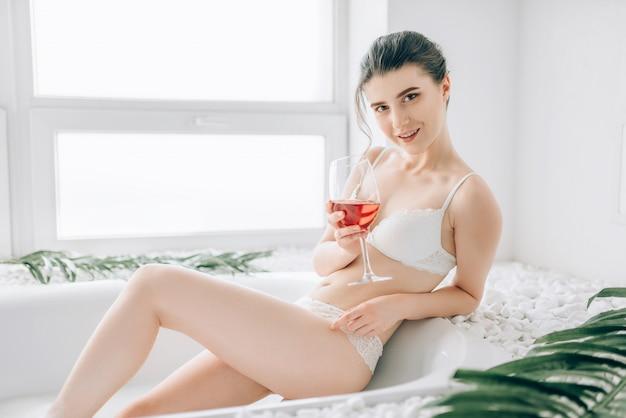 Kobieta siedzi w wannie z lampką wina