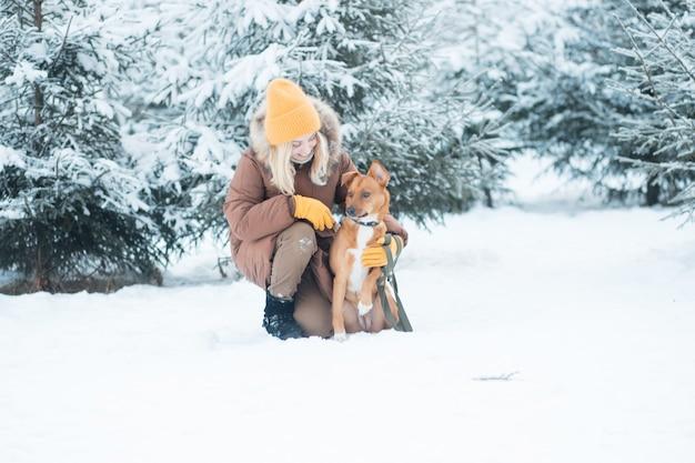 Kobieta siedzi z czerwonym psem kundel w zimowym lesie.