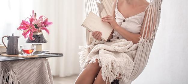 Kobieta siedzi z książką w fotelu hamakowym. koncepcja wypoczynku i domowego komfortu.