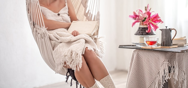 Kobieta siedzi z książką w fotelu hamakowym. pojęcie wypoczynku i domowego komfortu.