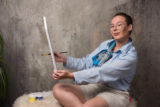 Kobieta siedzi z płótna i pędzla na tle marmuru. wysokiej jakości zdjęcie