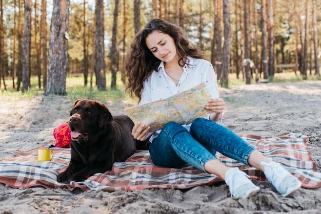 Kobieta siedzi z psem w przyrodzie