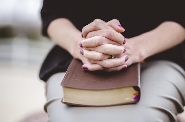 Kobieta siedzi z ręką na książce na kolanach