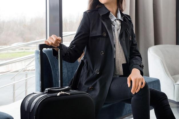 Kobieta siedzi z walizką w holu hotelu lub w poczekalni na lotnisku