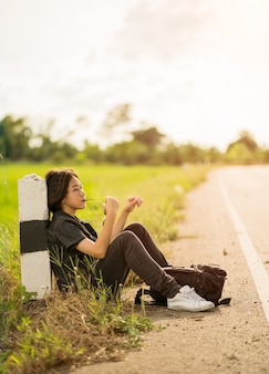 Kobieta siedzieć z plecakiem autostopem po drodze w okolicy