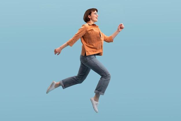 Kobieta skacząca na białym tle na niebiesko