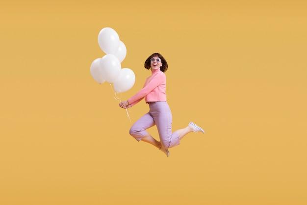 Kobieta skacząca na pomarańczowym tle