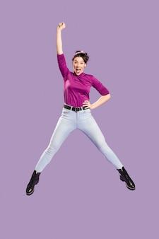 Kobieta skacze i ma jedno ramię nad głową