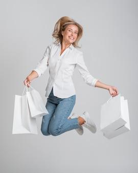 Kobieta skacze i pozuje, trzymając mnóstwo toreb na zakupy