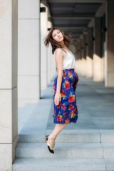 Kobieta skacze na ulicy. portret kobiety na zewnątrz w spódnicy kwiatowy i biały top.