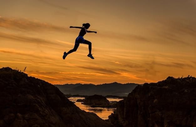 Kobieta skacze przez szczelinę między hill.woman przeskakując nad urwisko na tle zachodu słońca