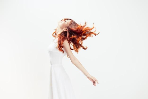 Kobieta skacze w białej sukni na białym tle